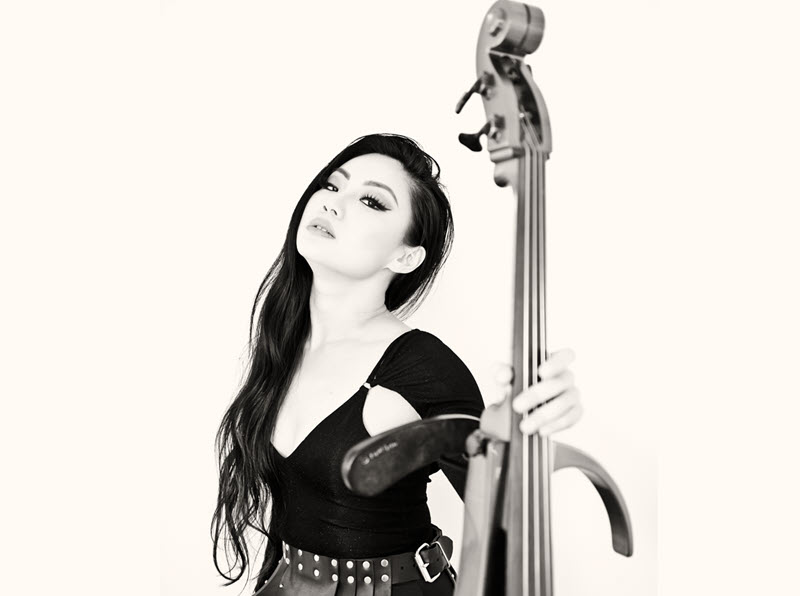 Young Asian woman with long hair, black shirt and leather skirt holding the neck of an open bodied electric cello.