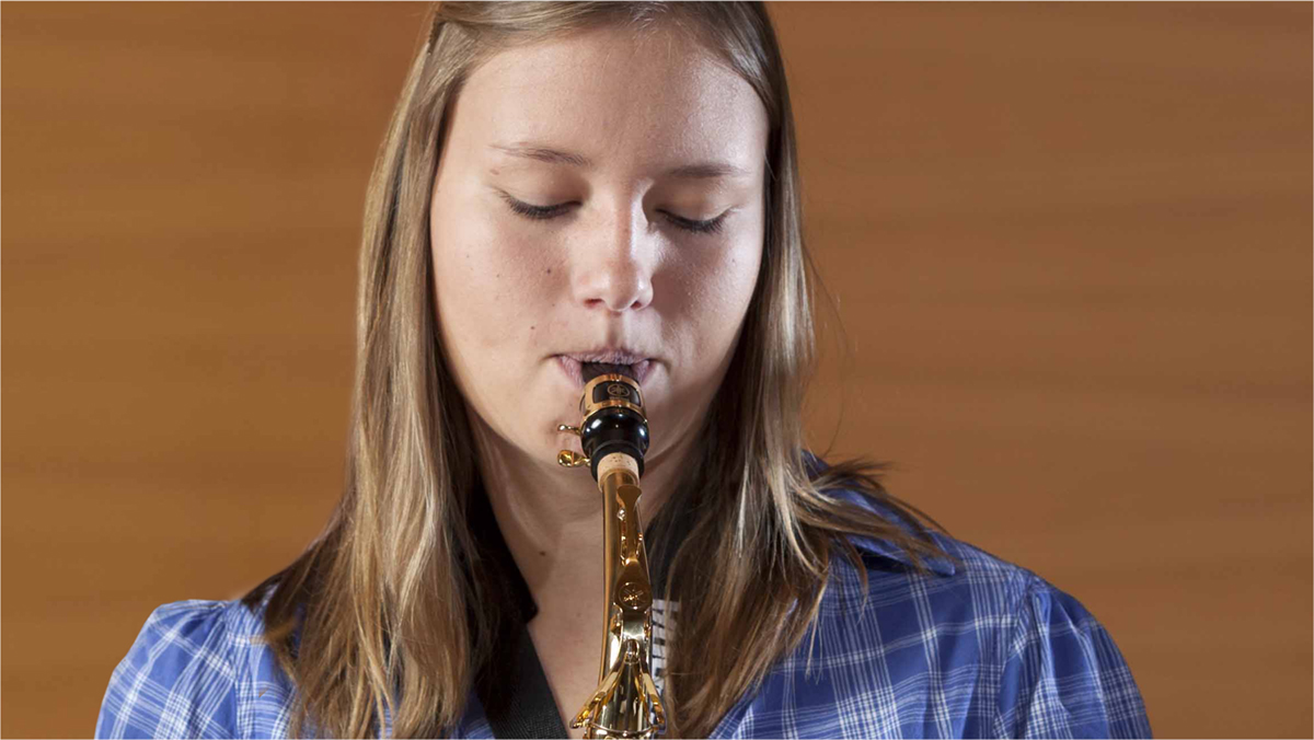 Young girl playing the saxophone.