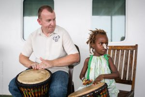 White man with young African Child playing hand drums.