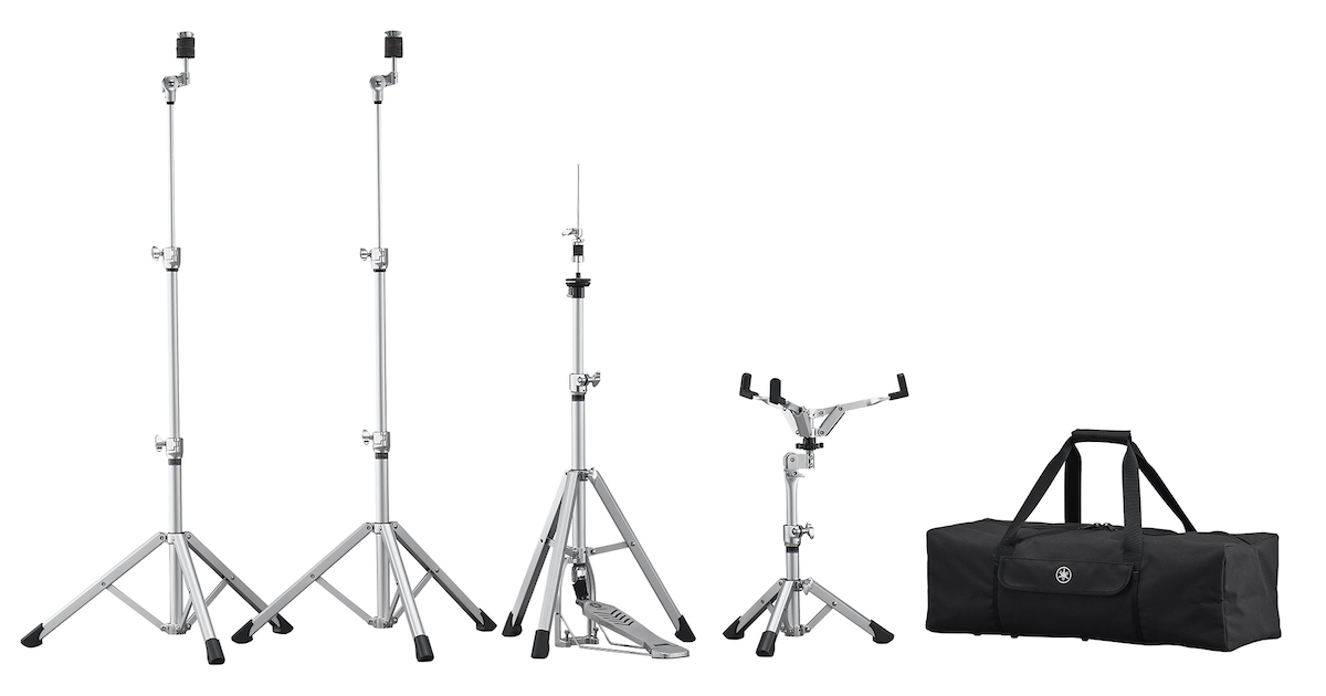 Four collapsible dram stands shown in various stages of being collapsed and their black rectangular carrying case.