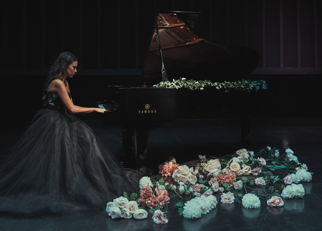 Young woman seen in profile playing a Yamaha concert grand piano on a darkened stage. There is a large flower arrangement in the foreground.