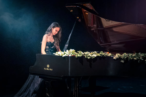 Young woman in ball gown seen in profile playing a Yamaha concert grand piano on darkened stage.