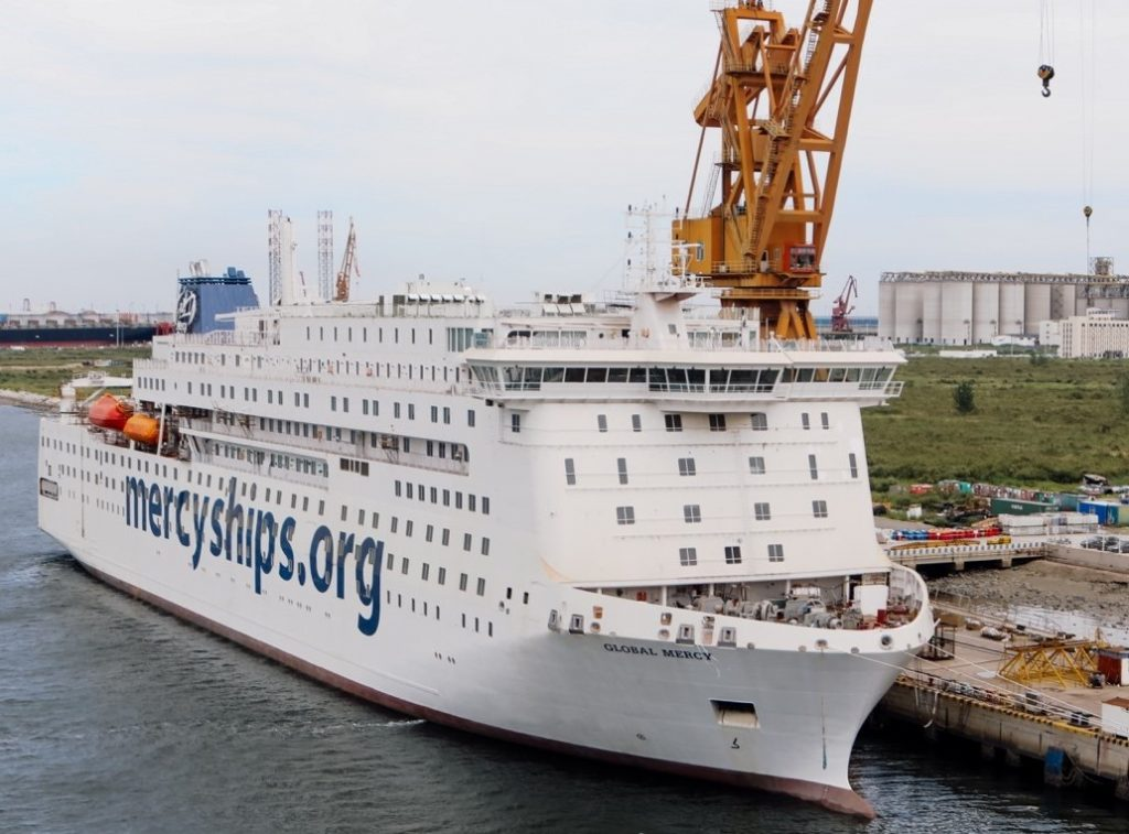 """Large white passenger ship in dock with a crane in the background. The words """"mercyships.org"""" is painted on the side of the ship."""