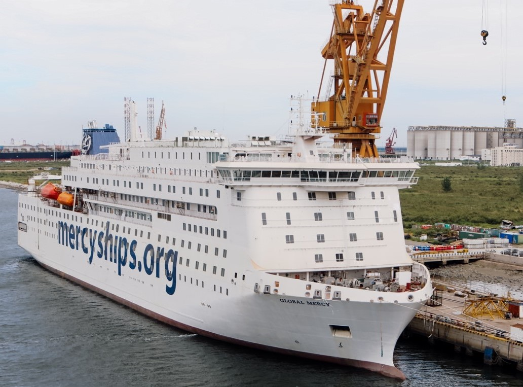 """Large white passenger ship docked with """"mercyships.org"""" painted on its side."""