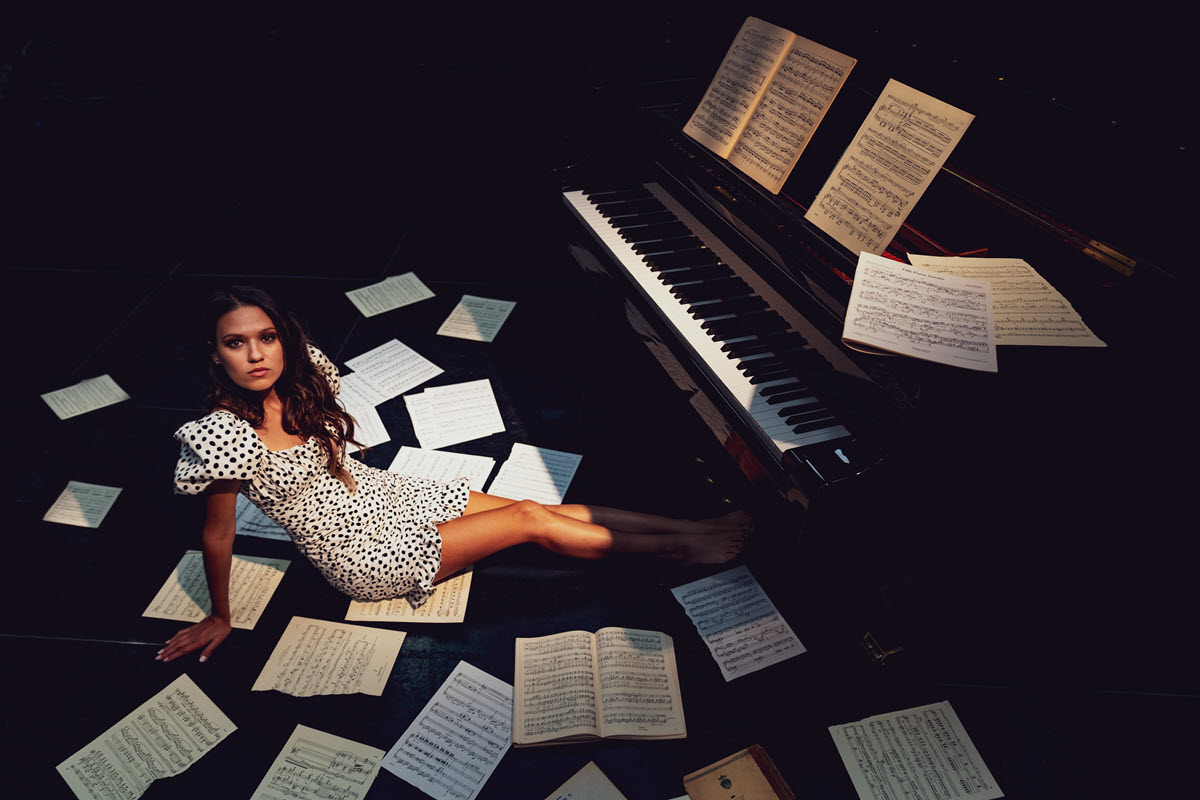 Young woman in a dress sitting on the floor surrounded by scattered sheet music next to a grand piano that has more sheet music on the stand.