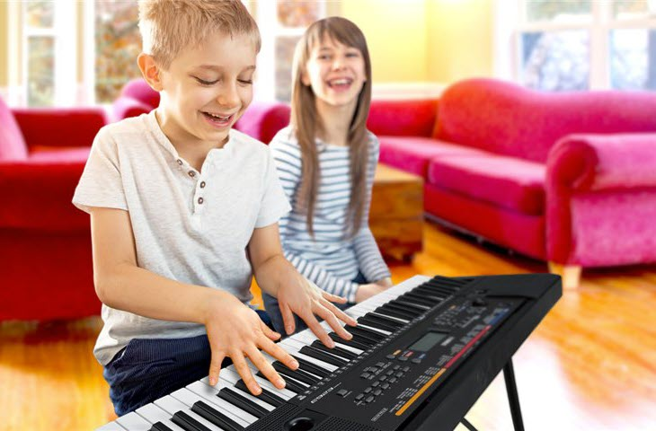 A young boy is happily playing a digital piano keyboard in his living room with his sister nearby.