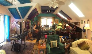 Beth's home studio with pianos, keyboards, guitars and decorative string lights.