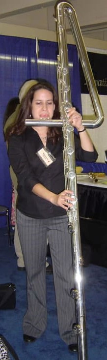 Woman playing contrabass flute which 50% taller than she is.