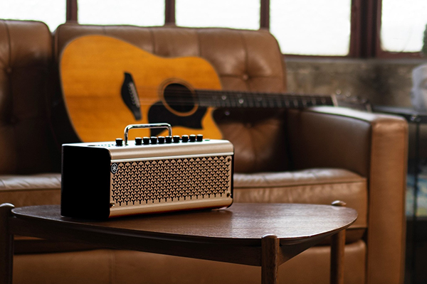Yamaha THR30IIA desktop amp on wooden coffee table with acoustic guitar in background.