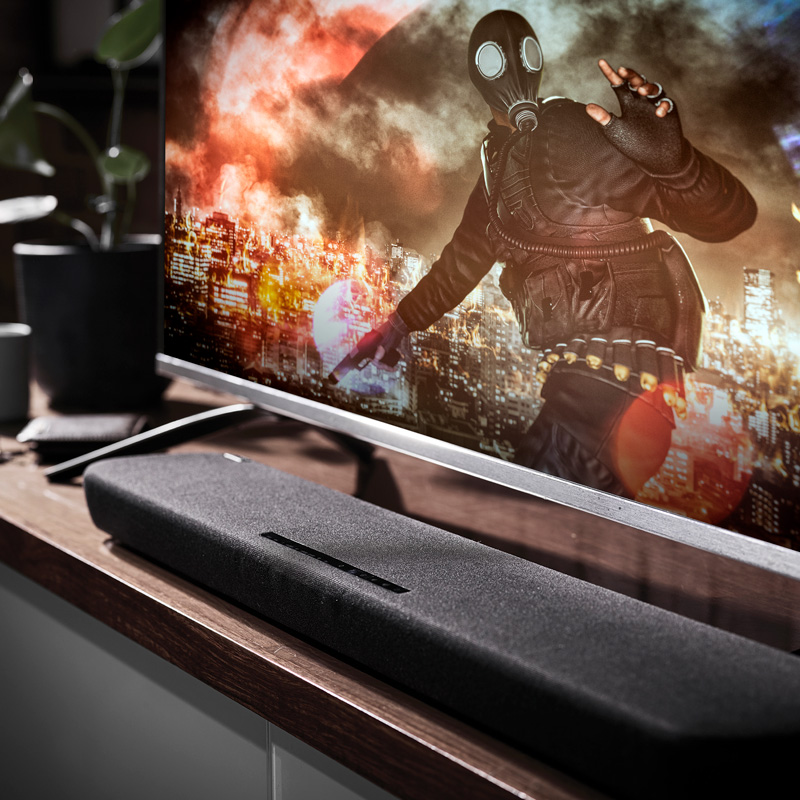 Closeup of television screen sitting on a table with a long thin speaker on table directly below.