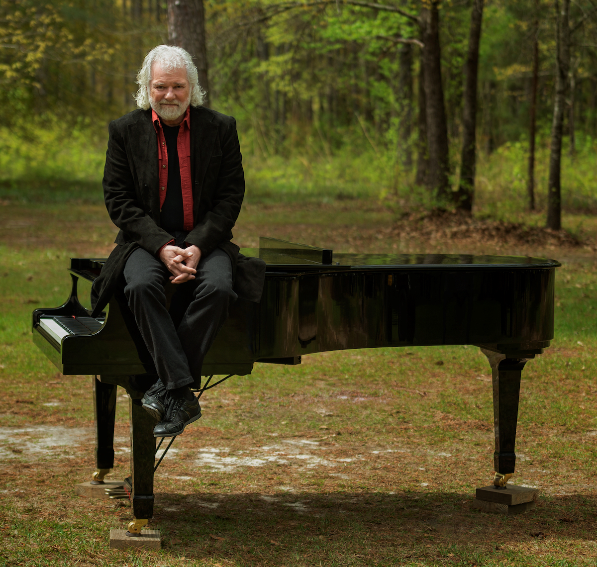 Chuck Leavell sitting on piano in field.
