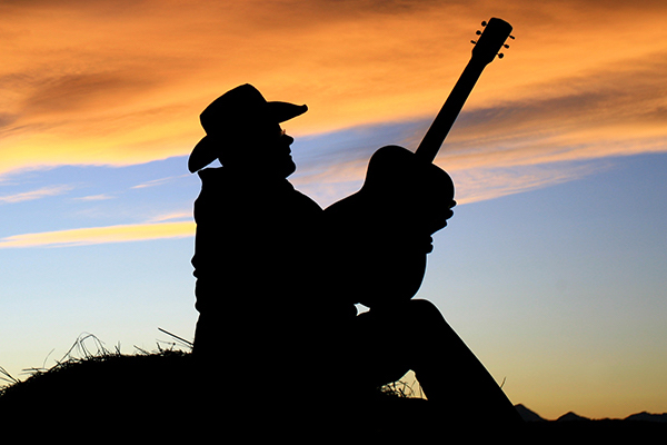 Country musician plays guitar at sunset.