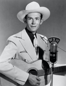 Black and white portrait of Hank Williams with a guitar.