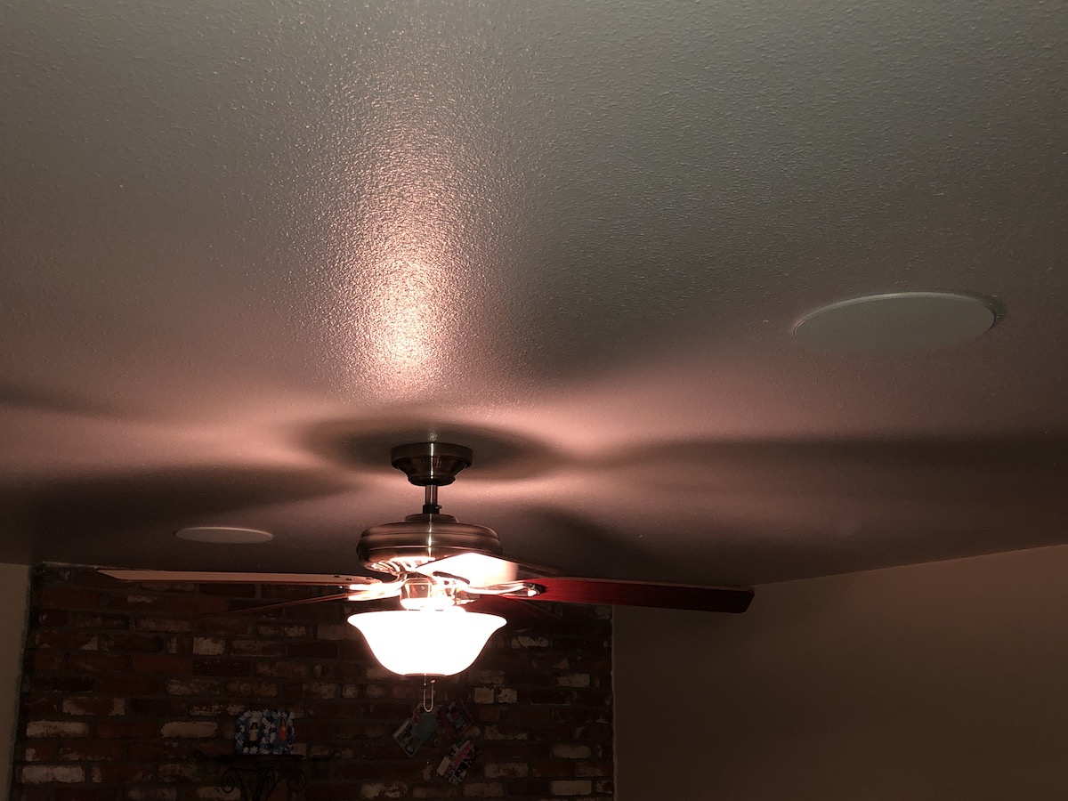 Installed in-ceiling speaker to the right and left of a lighted ceiling fan.