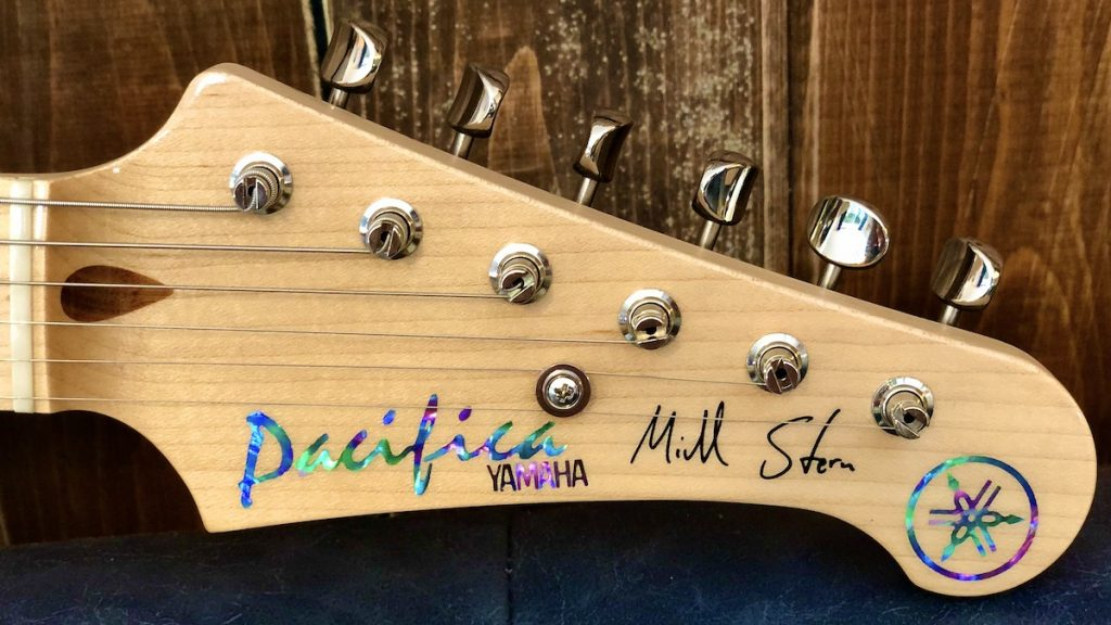 Electric guitar headstock with Mike Stern's signature and abalone inlays.