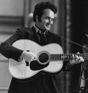 Merle Haggard playing guitar.