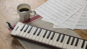 Yamaha Pianica keyboard wind instrument on table with coffee cup.
