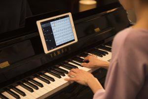 Woman playing Yamaha piano with iPad on music stand.