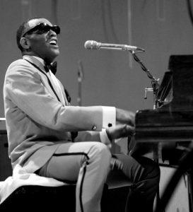 Ray Charles playing piano and singing.
