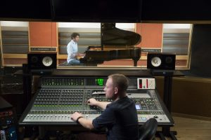 Man behind mixing desk recording a pianist in a sound booth.