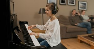 A smiling little girl playing a SILENT piano while wearing headphones.
