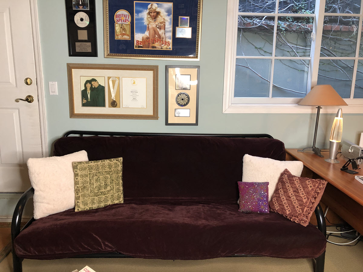 Purple futon couch with framed awards hanging on wall above it.