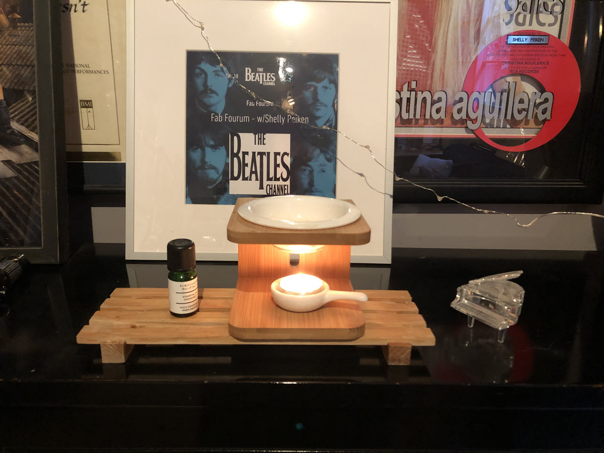 Table with a basin with a bottle of essential oils and a candle. A Beatles' poster on the wall in the background.