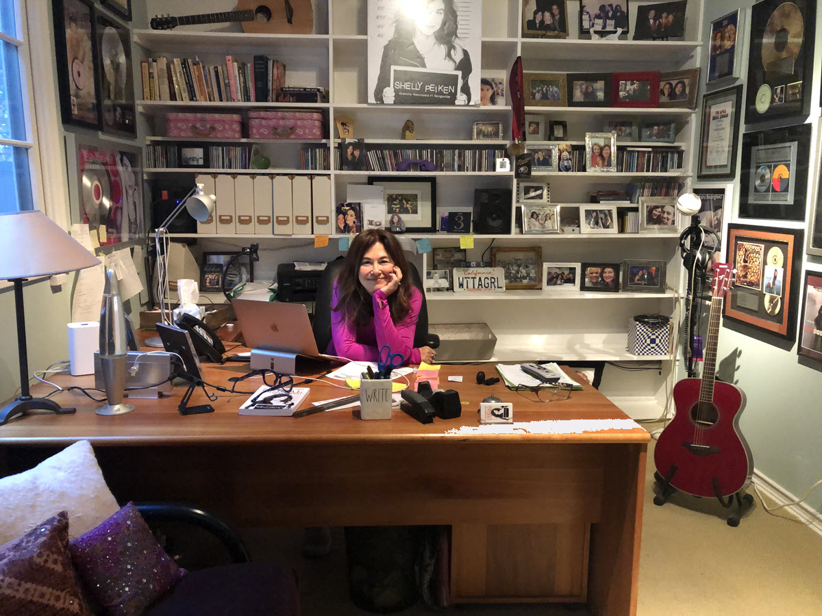 Woman with dark hair smiling at camera sitting behind a wooden desk with wall of shelving behind her full of books, pictures and albums. There is an acoustic guitar on a stand on her left.