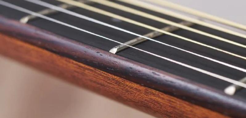 Close up of a guitar neck with strings.