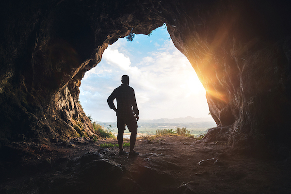 View of the silhouette of a person coming out of a dark cave into the bright sunlight.