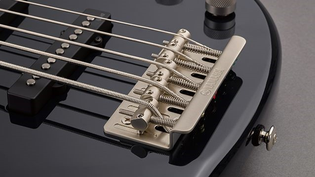 Closeup view of an electric bass' strings stretched over the saddle and the screw at the bottom of the instrument body for adjusting.