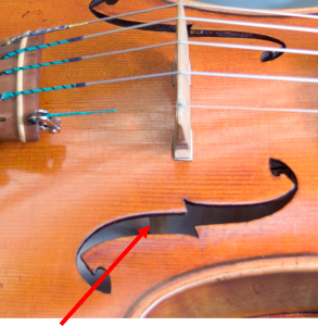 Close-up of a violin with a red arrow pointing to its sound post.