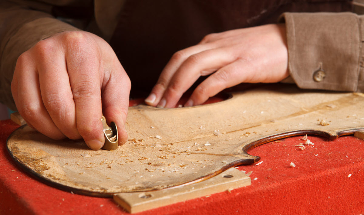 Close-up image of hands using small tools on a piece of wood shaped like a violin.
