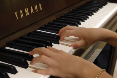Woman's hands playing a Yamaha piano keyboard.