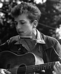 Young Bob Dylan singing and playing guitar with a harmonica around his neck.