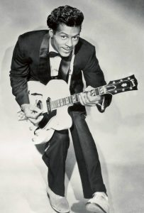 Chuck Berry posing in his duck walk with his guitar.