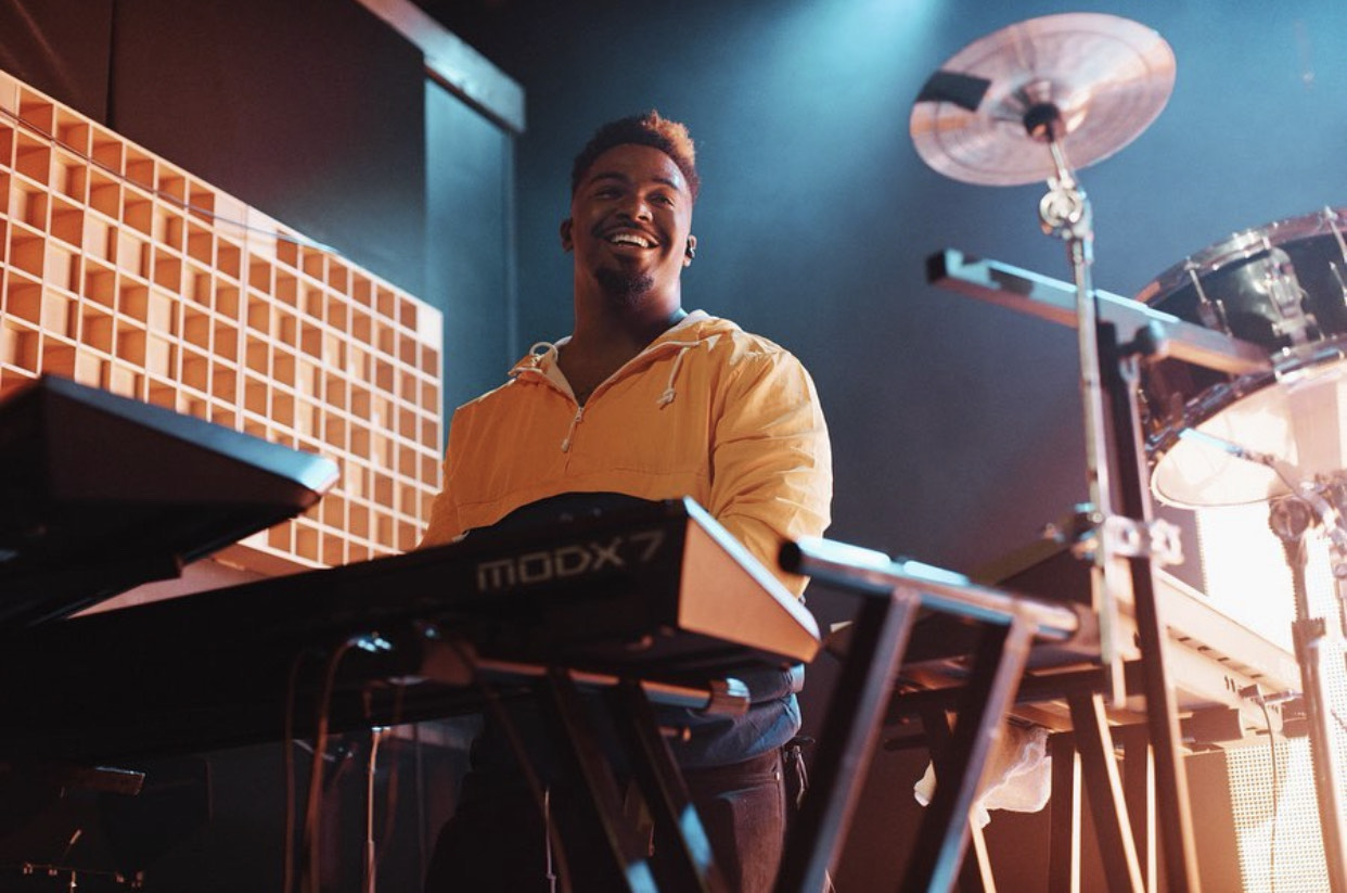 Smiling man with brown skin wearing orange sweater on stage at a synthesizer keyboard.