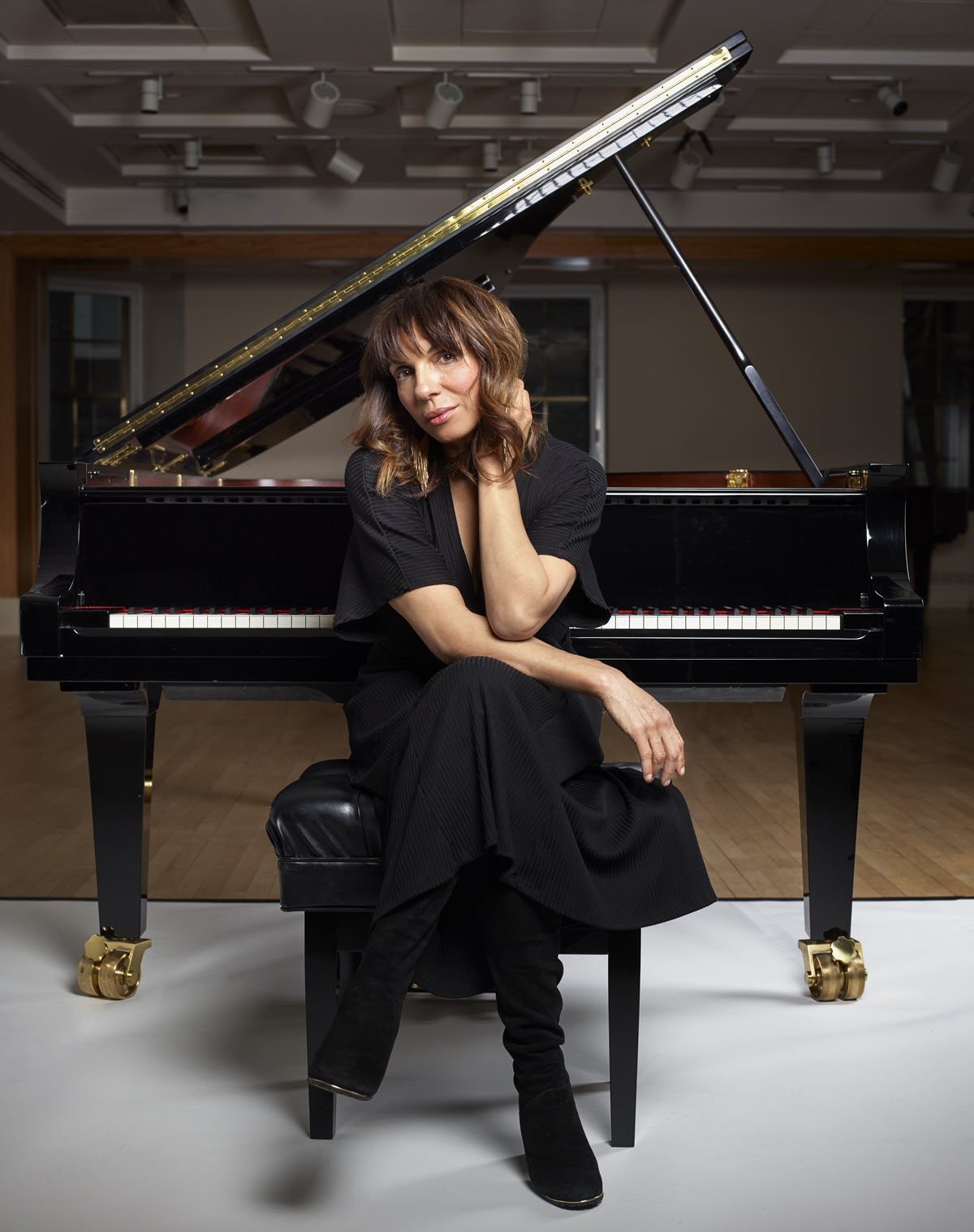 Woman in a black dress and suede boots seated casually with her legs crossed an her head resting lightly on her hand on a piano bench with a grand piano open behind her.