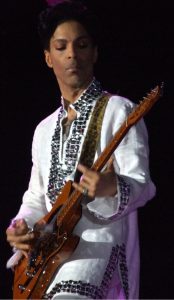 Prince playing guitar on stage.