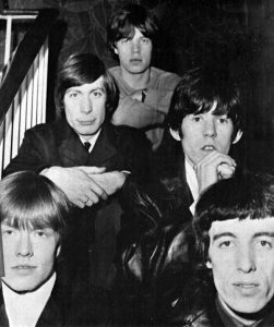 Closeup of The Beatles sitting on a staircase.