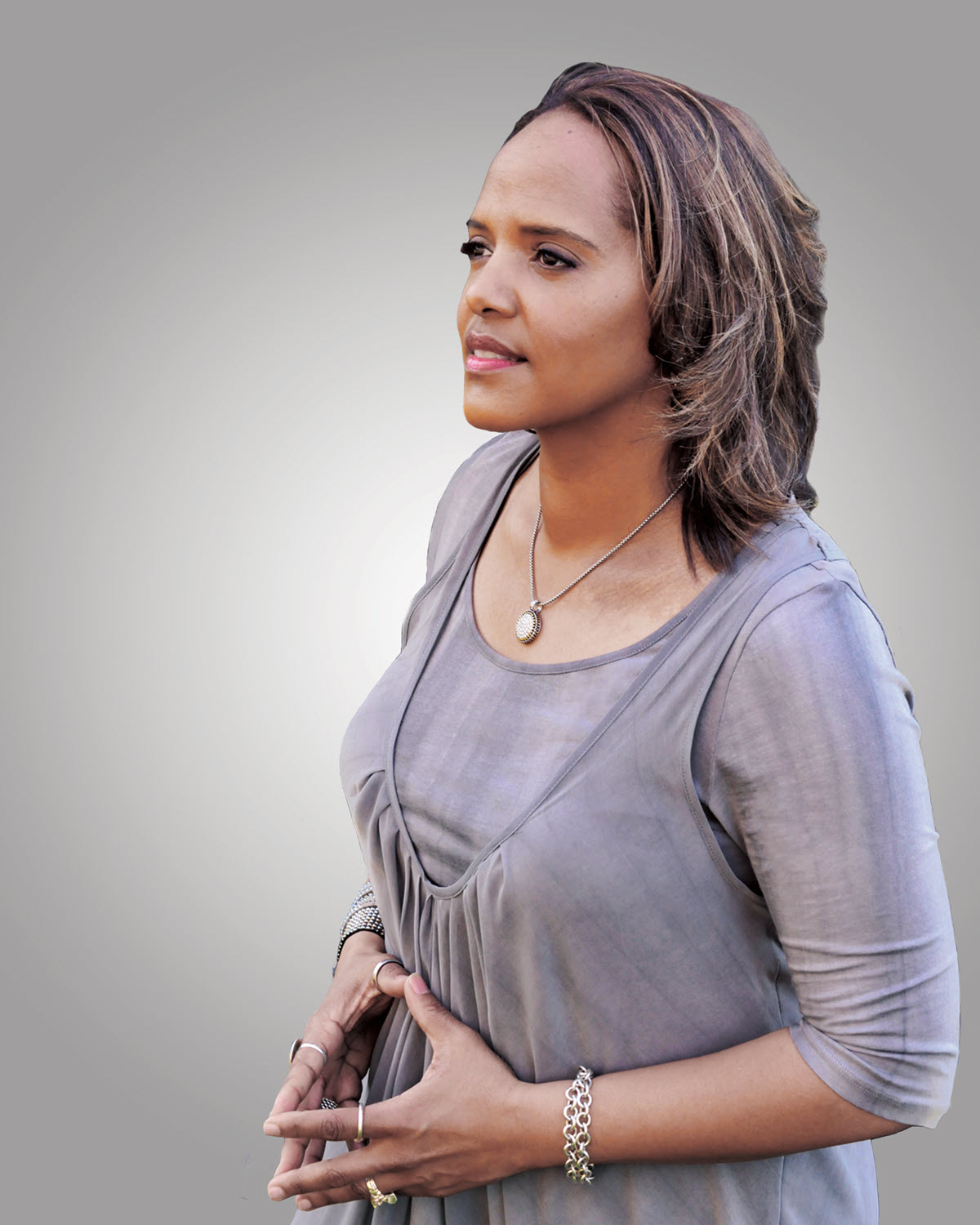 Beautiful woman seen in 3/4 profile. She has shoulder length ash brown hair, light brown skin. She is wearing a short sleeved sweater set and wearing silver necklace and rings.