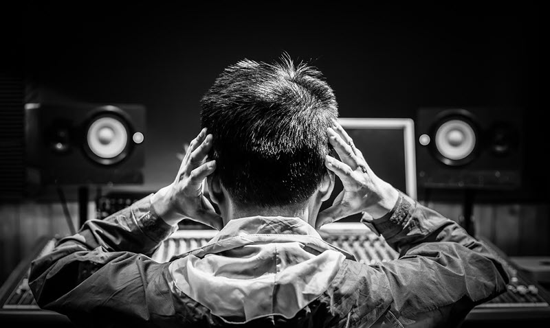 View from behind of a man putting his hands where his headset would be and is seated in front of a mixing board.