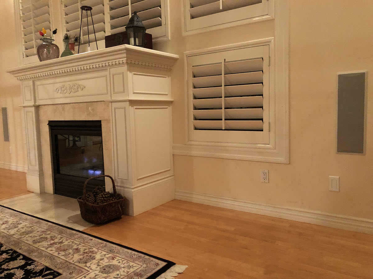 View of two speakers flanking a fireplace in a living room.