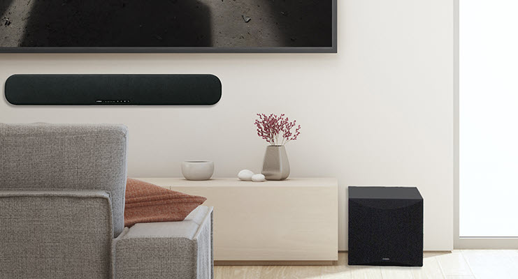 Modern living room with subwoofer on floor and a sound bar installed on wall below flat screen facing couch.