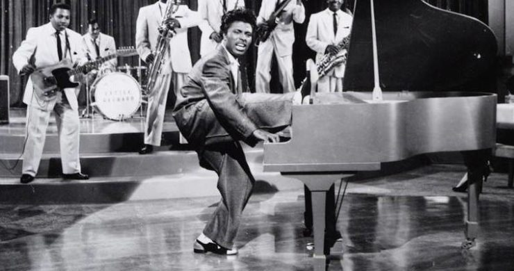 Little Richard performing on stage, playing the piano with one foot on the piano and his band playing in background.