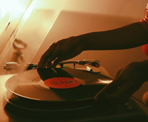 Young woman playing her vinyl collection at home.