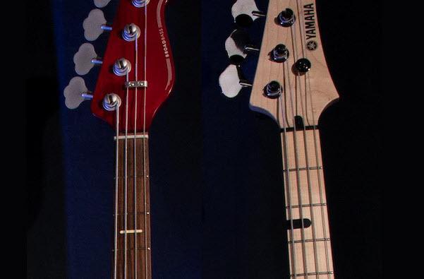 Closeup of two electric bass guitar necks.