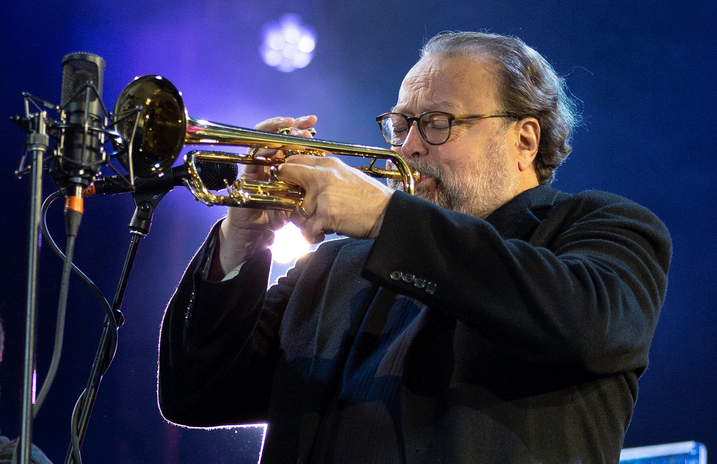 Man blowing a trumpet onstage.