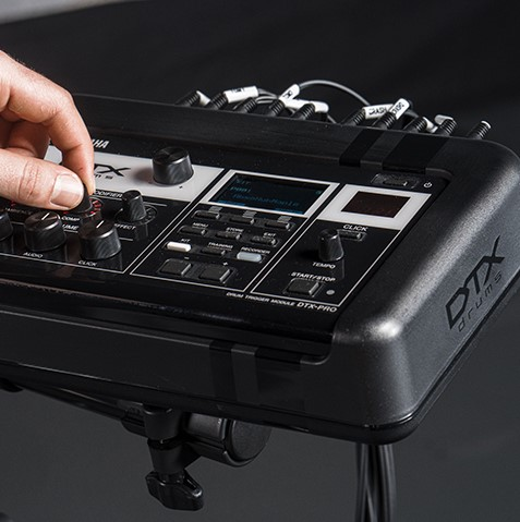 Closeup of someone's hand adjusting the controls of an electronic drum kit.