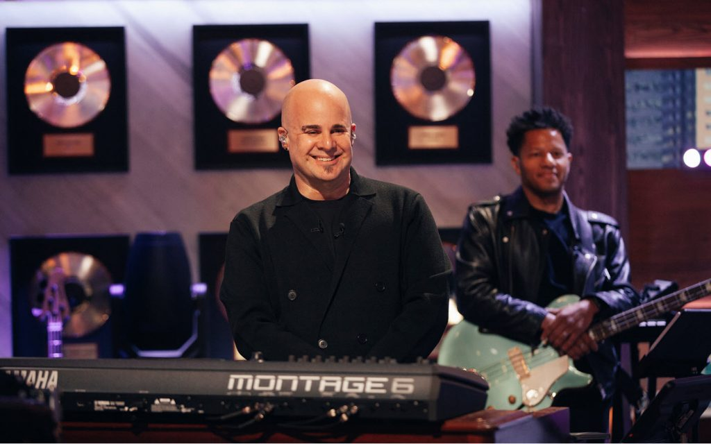 Attractive bald male musician with a guitarist in the background an a wall of framed gold albums smiles for camera.